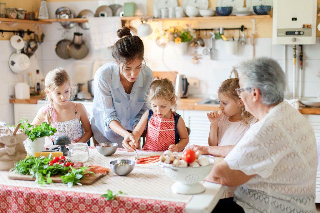 Family are cooking italian pizza in cozy home kitchen for dinner. Cute kids and grandmother are preparing homemade food. Old senior woman is teaching three girls. Children chef concept. (Family are cooking italian pizza in cozy home kitchen for dinner